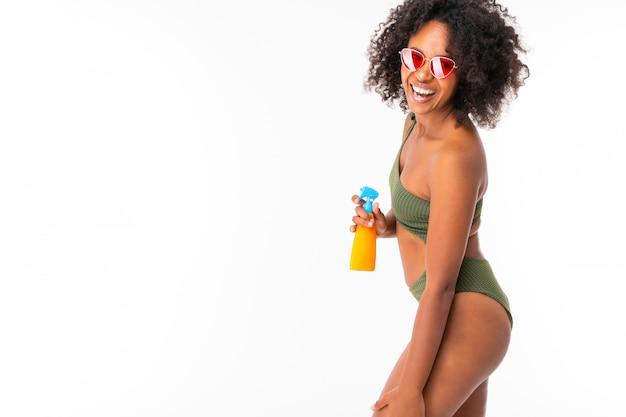 Africano con occhiali da sole in un costume da bagno verde su bianco