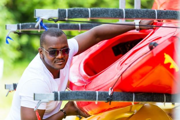 Afrikanischer mann entlädt kajak vom bootsanhänger
