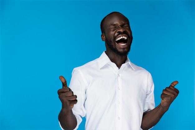Afro-americano barbuto in camicia bianca che ride