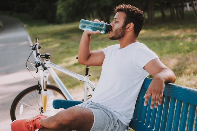 Afro guy beve l'acqua sulla panchina accanto alla bicicletta