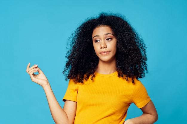 Afroamericano della donna in una maglietta nello studio su una posa colorata