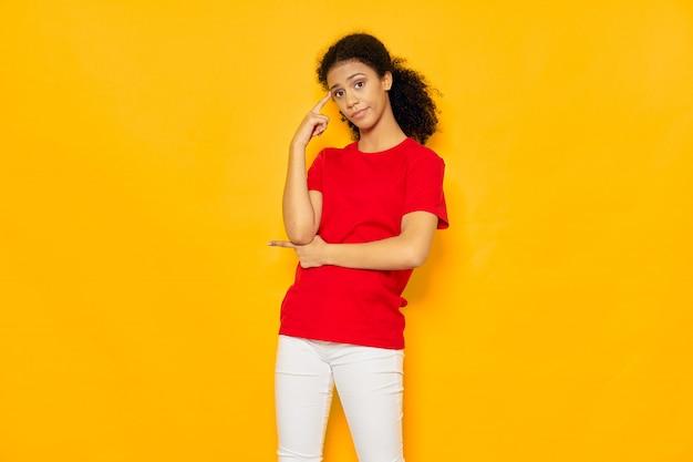 Afroamericano della donna in una maglietta nello studio su una posa di superficie colorata
