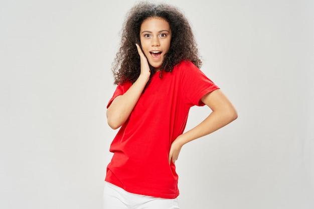 Afroamericano della donna in uno spazio della maglietta su una posa dello spazio colorato