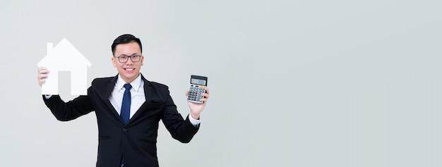 Agente asiatico dell'uomo che mostra il modello della casa con il calcolatore