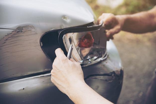 Agente assicurativo che lavora durante il processo di reclamo in loco in caso di incidente d'auto, persone e assicurazione auto