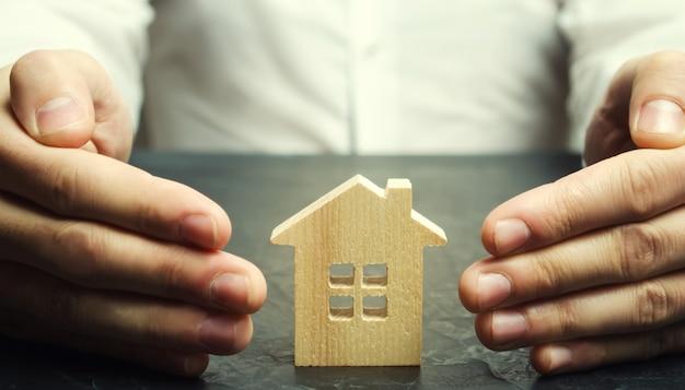 Agente assicurativo protegge la casa con un gesto di protezione. il concetto di assicurazione sulla proprietà