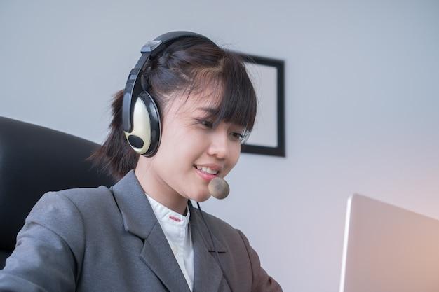 Agente della giovane donna asiatica o agente del centro di chiamata con le cuffie avricolari che funzionano