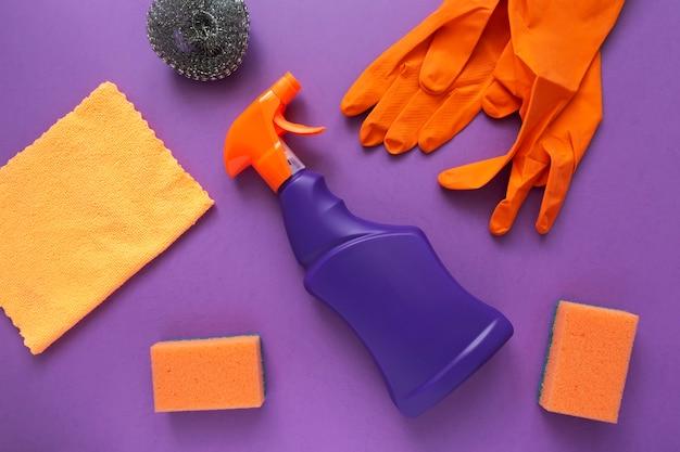 Agente detergente e detergente, spugne, tovaglioli e guanti di gomma, sfondo viola.