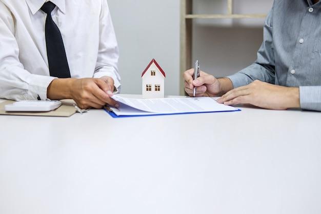 Agente di brokeraggio immobiliare che presenta e si consulta al cliente all'assicurazione del segno decisionale