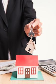 Agente di cambio casa chiave di cambio con il cliente dopo il contratto di accordo di vendita a casa.