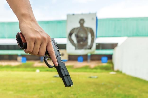 Agente di polizia che tiene una pistola di applicazione della legge