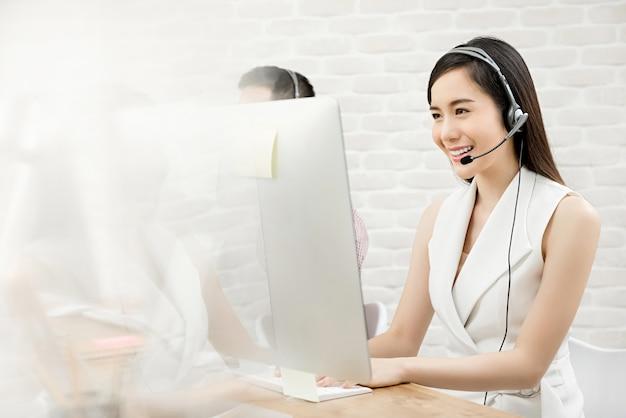 Agente di servizio di assistenza al cliente di telemarketing della bella donna asiatica che lavora nella call center