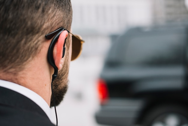 Agente di sicurezza del primo piano che verifica l'automobile