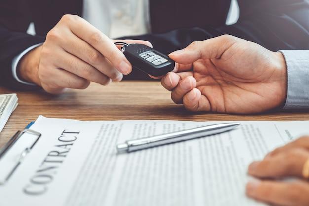 Agente di vendita che fornisce la chiave dell'automobile al cliente e firma il contratto di accordo, automobile di assicurazione.