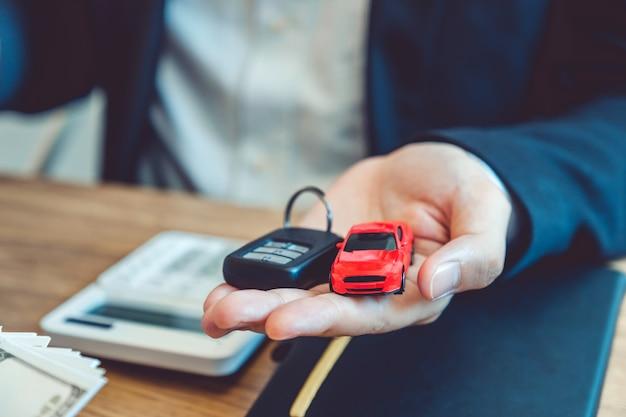 Agente di vendita che fornisce la chiave dell'automobile al cliente e firma il contratto di accordo, concetto dell'automobile di assicurazione.