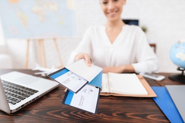 Agente di viaggio mantiene i biglietti per l'aereo nell'agenzia di viaggi
