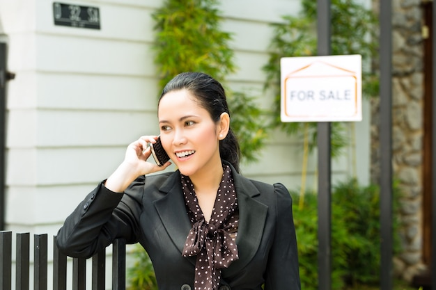 Agente immobiliare asiatico che presenta una nuova casa