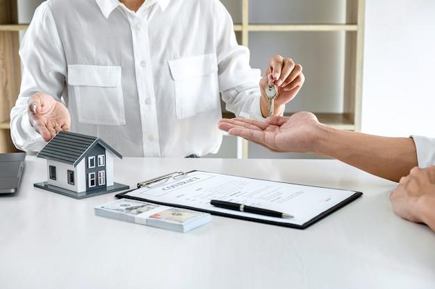 Agente immobiliare che consegna la chiave al cliente dopo aver firmato il contratto di locazione