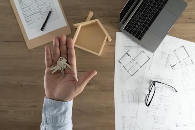 Agente immobiliare che firma un contratto sopra un mutuo per la casa del bene immobile di chiave della casa