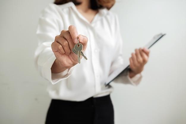 Agente immobiliare che fornisce le chiavi al cliente per il contratto di affare per comprare casa.