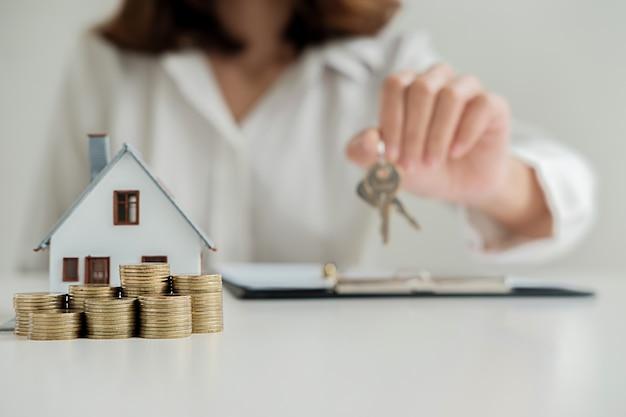 Agente immobiliare che fornisce le chiavi al cliente per il contratto di affare per l'acquisto di una casa,