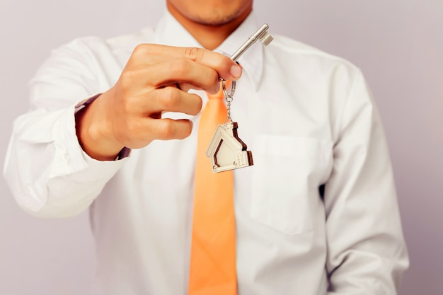 Agente immobiliare che fornisce le chiavi della casa, fondo isolato,