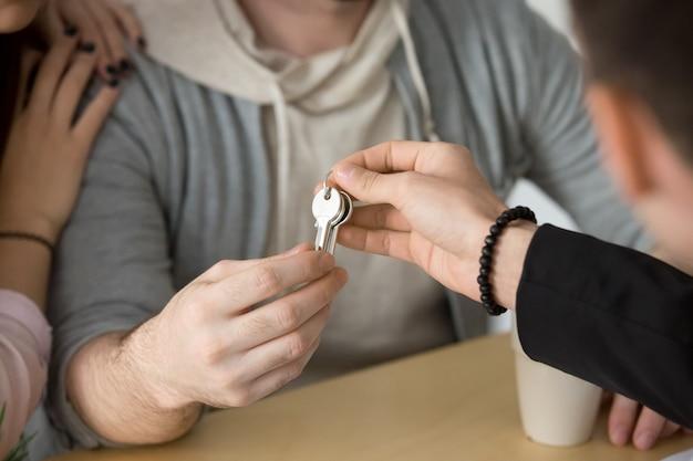 Agente immobiliare che fornisce le chiavi delle coppie, compranti il concetto della nuova casa, fine su