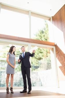 Agente immobiliare che interagisce con la giovane donna che mostra nuova casa