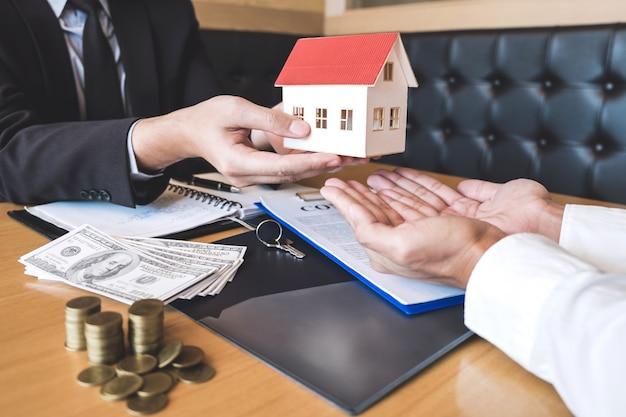 Agente immobiliare che invia il modello di casa al cliente dopo aver firmato un contratto di contratto immobiliare con modulo di richiesta di mutuo approvato, relativo all'offerta di mutuo ipotecario e all'assicurazione casa