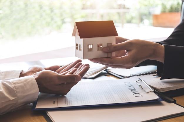 Agente immobiliare che invia un modello di casa al cliente dopo aver firmato un contratto di contratto immobiliare con modulo di richiesta di mutuo approvato, relativo all'offerta di mutuo ipotecario e all'assicurazione casa
