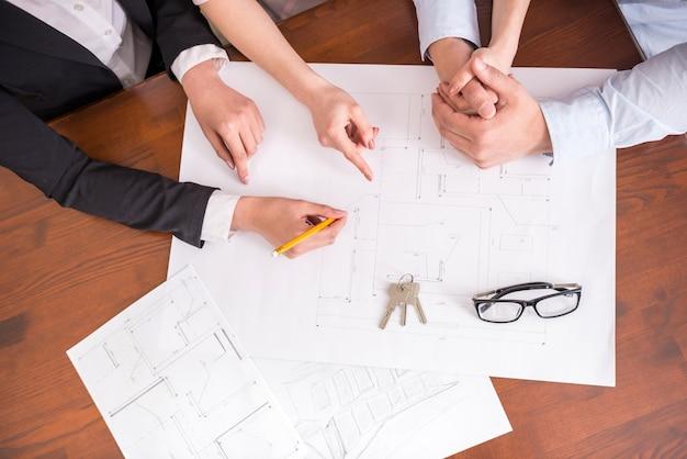 Agente immobiliare che mostra il contratto con la disposizione del pavimento in un appartamento.