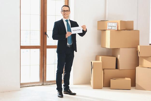 Agente immobiliare che tiene nuovo appartamento con scatole di cartone.