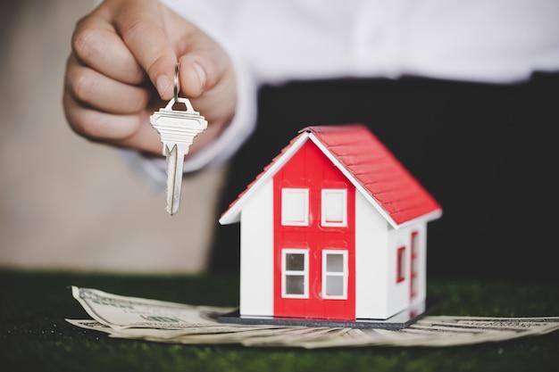 Agente immobiliare con modello di casa e chiavi