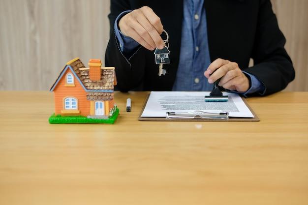 Agente immobiliare con timbro della chiave di casa approvato sul documento di contratto di mutuo ipotecario