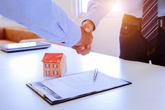 Agente immobiliare e cliente che stringono le mani dopo aver firmato un contratto.