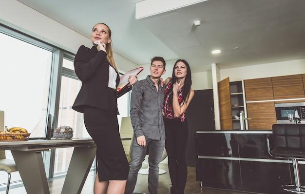Agente immobiliare e giovani coppie che fanno affari per un nuovo appartamento di lusso