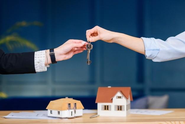 Agente immobiliare femminile che fornisce la chiave dal nuovo appartamento, casa ai clienti femminili.