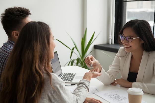 Agente immobiliare femminile che fornisce le chiavi alle coppie emozionanti