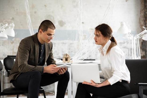 Agente immobiliare femminile che mostra nuova casa ad un giovane dopo una discussione sui programmi della casa, muoversi, nuovo concetto domestico
