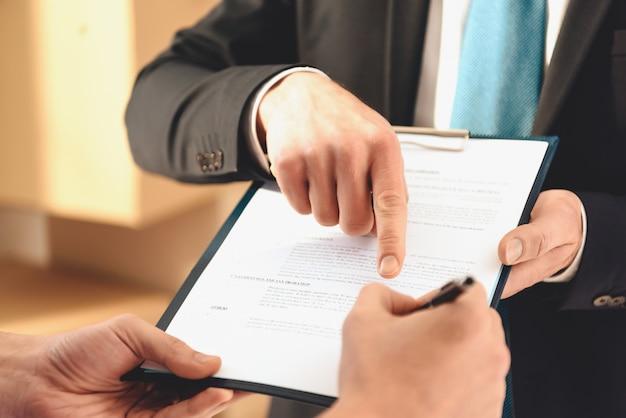 Agente immobiliare mostra il dito dove è necessario firmare.