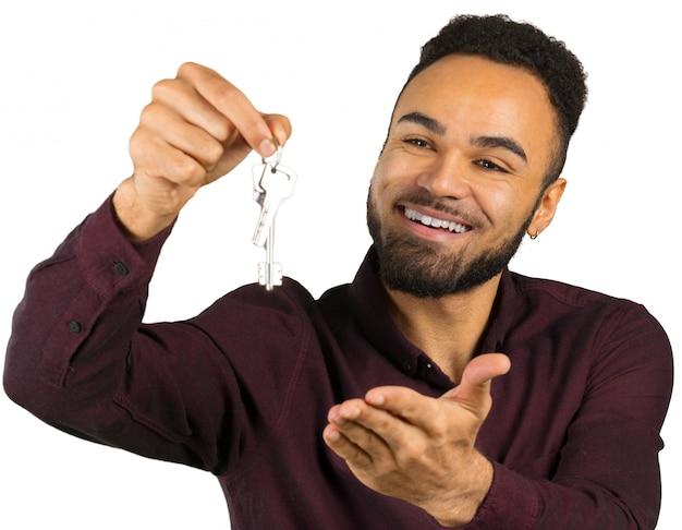 Agente immobiliare o proprietario di uomo di colore positivo felice di una nuova casa che tiene le sue chiavi isolate su bianco