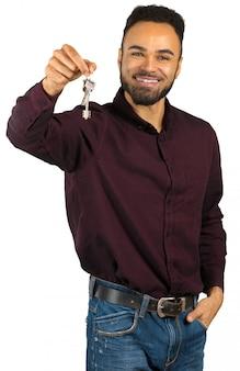 Agente immobiliare positivo felice dell'uomo di colore o proprietario di nuova casa che giudica le sue chiavi isolate