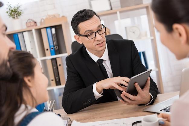 Agente immobiliare rappresentativo aiuta la giovane famiglia a vendere immobili.