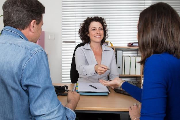 Agente immobiliare sicuro della donna che fornisce chiave di nuovo appartamento al cliente.