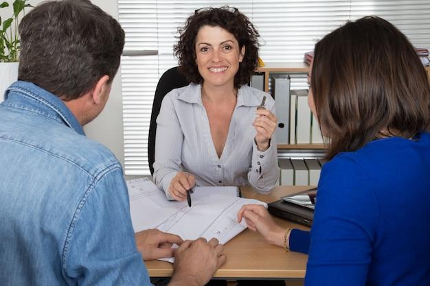 Agente immobiliare sorridente della donna che fornisce chiave di nuovo appartamento al cliente.