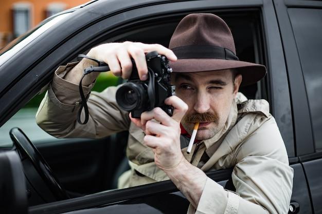 Agente investigativo che fuma una sigaretta nella sua automobile mentre spia qualcuno con la sua macchina fotografica