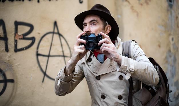 Agente investigativo che scatta foto in una baraccopoli con la sua macchina fotografica vintage