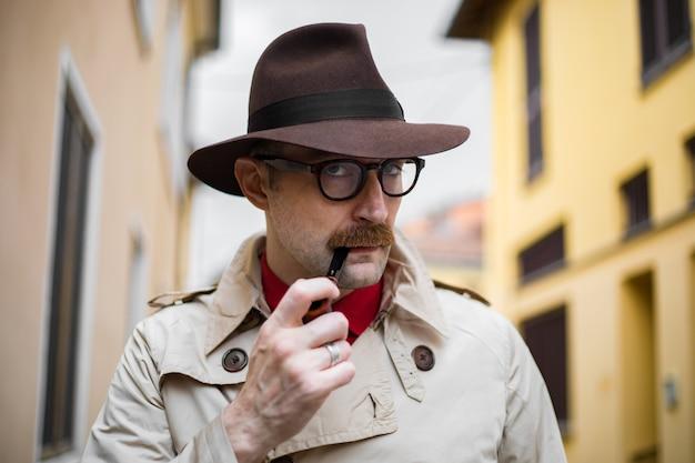 Agente investigativo d'annata che fuma una pipa all'aperto in un ambiente grungy