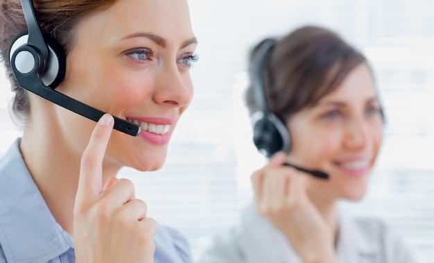 Agenti del call center con auricolari al lavoro