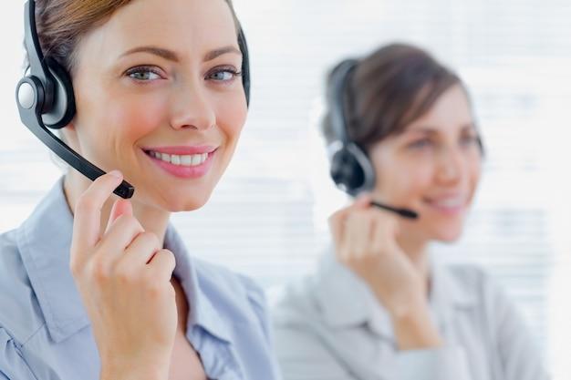 Agenti di call center sorridenti con cuffie al lavoro